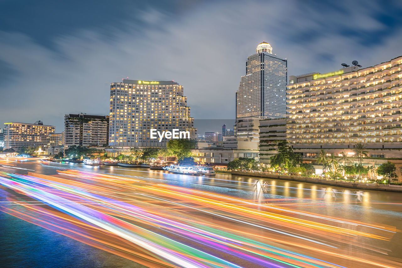long exposure, motion, architecture, speed, light trail, building exterior, illuminated, city, night, blurred motion, sky, built structure, outdoors, skyscraper, cityscape, no people, road, modern, water