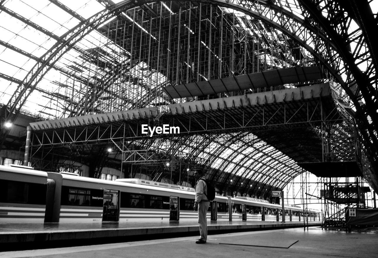 railroad station, railroad station platform, architecture, built structure, roof, rail transportation, indoors, real people, modern, day