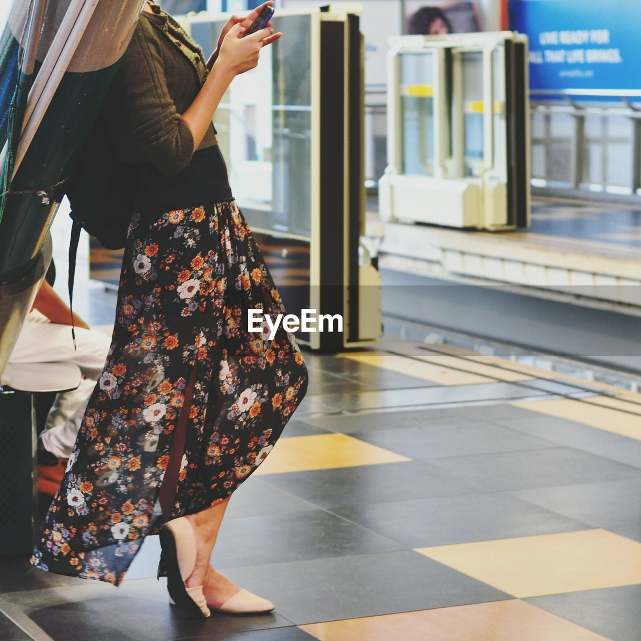Low section of woman using mobile phone on railroad station platform