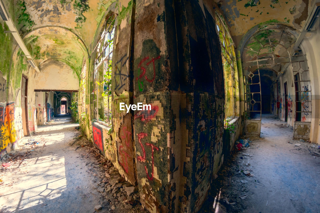 architecture, built structure, building, day, no people, arch, abandoned, building exterior, the way forward, direction, old, damaged, outdoors, city, run-down, decline, nature, graffiti, street, deterioration, architectural column