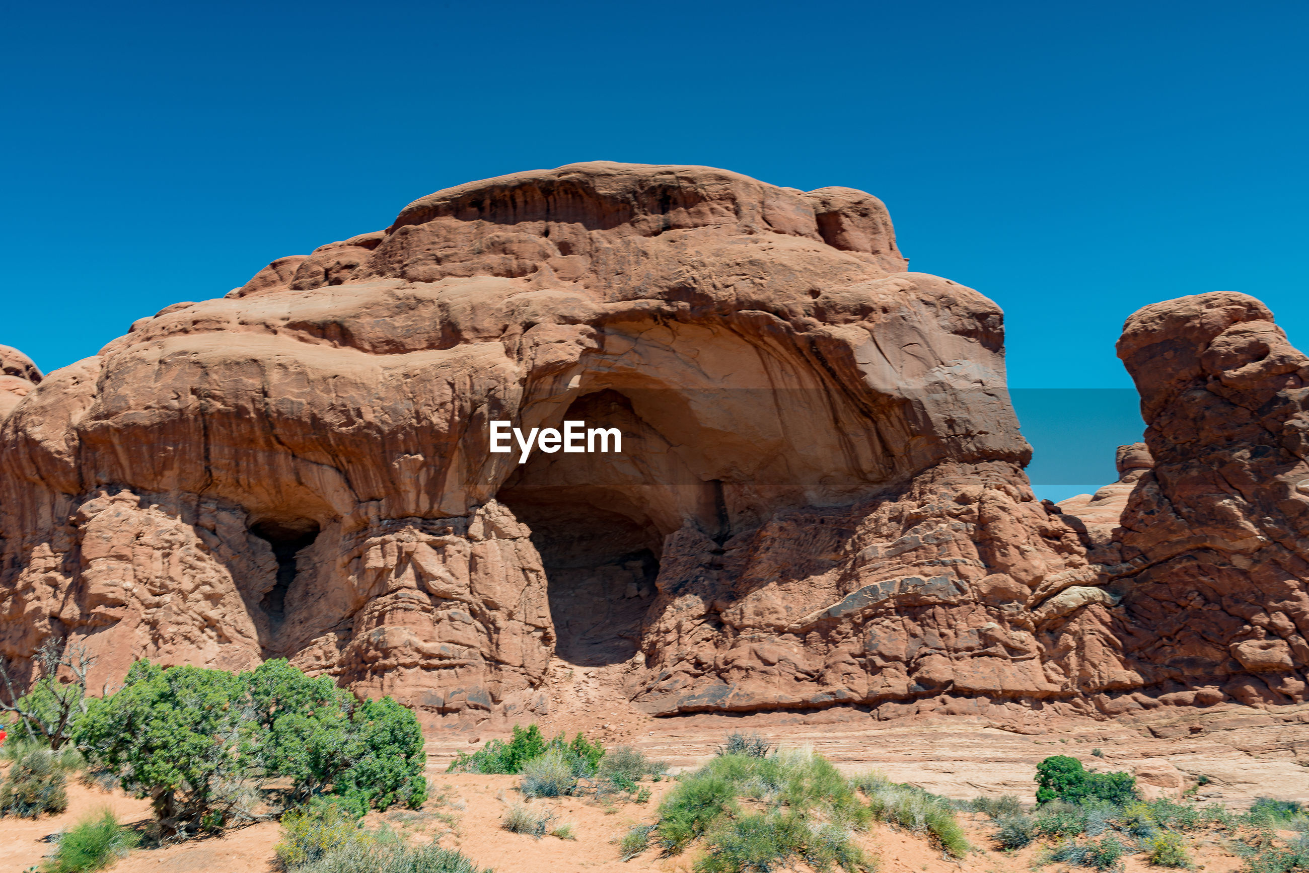 Low angle view of rock formation against blue sky on sunny day