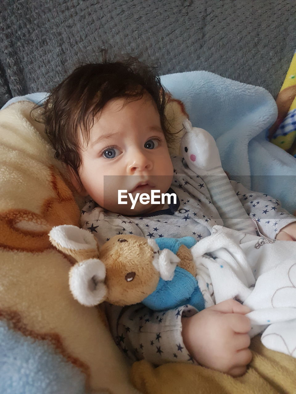 Portrait of baby girl lying with toy on bed at home