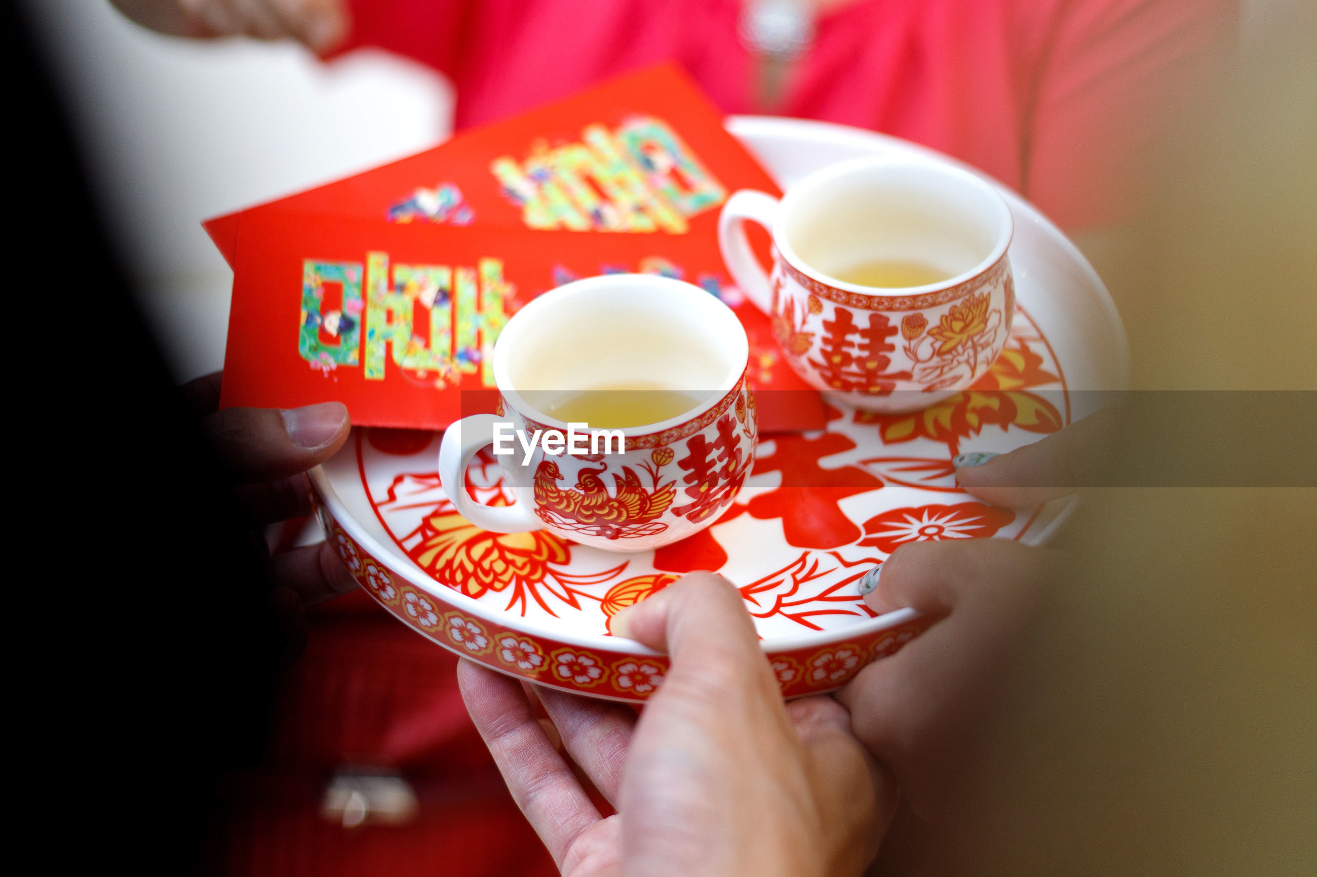 Cropped hands of people holding chinese wedding tea in tray
