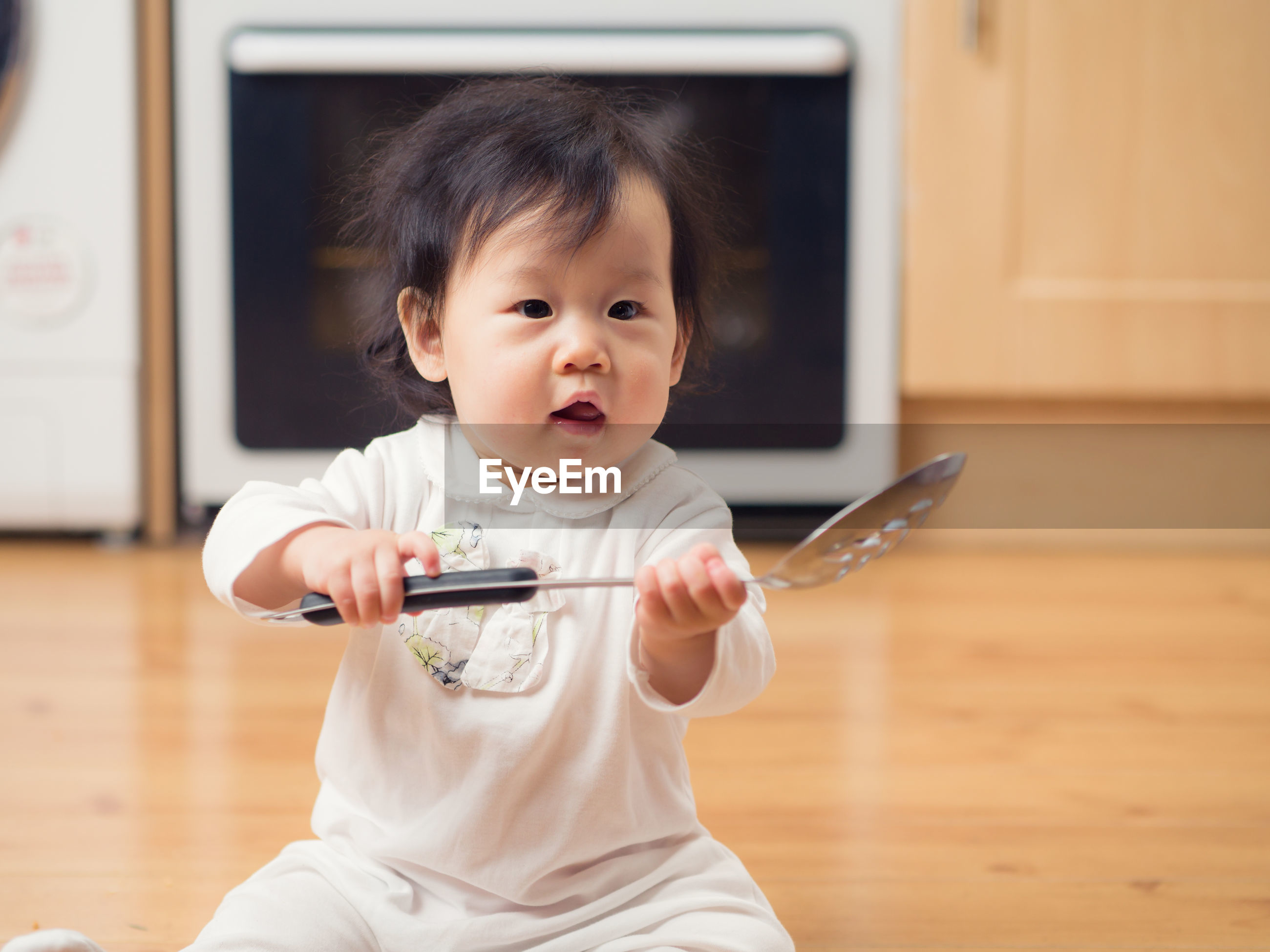 Cute boy playing with colander at home