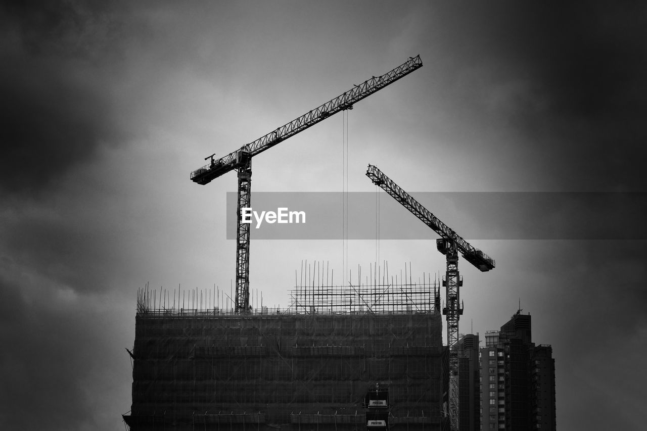 LOW ANGLE VIEW OF CRANES AGAINST BUILDING