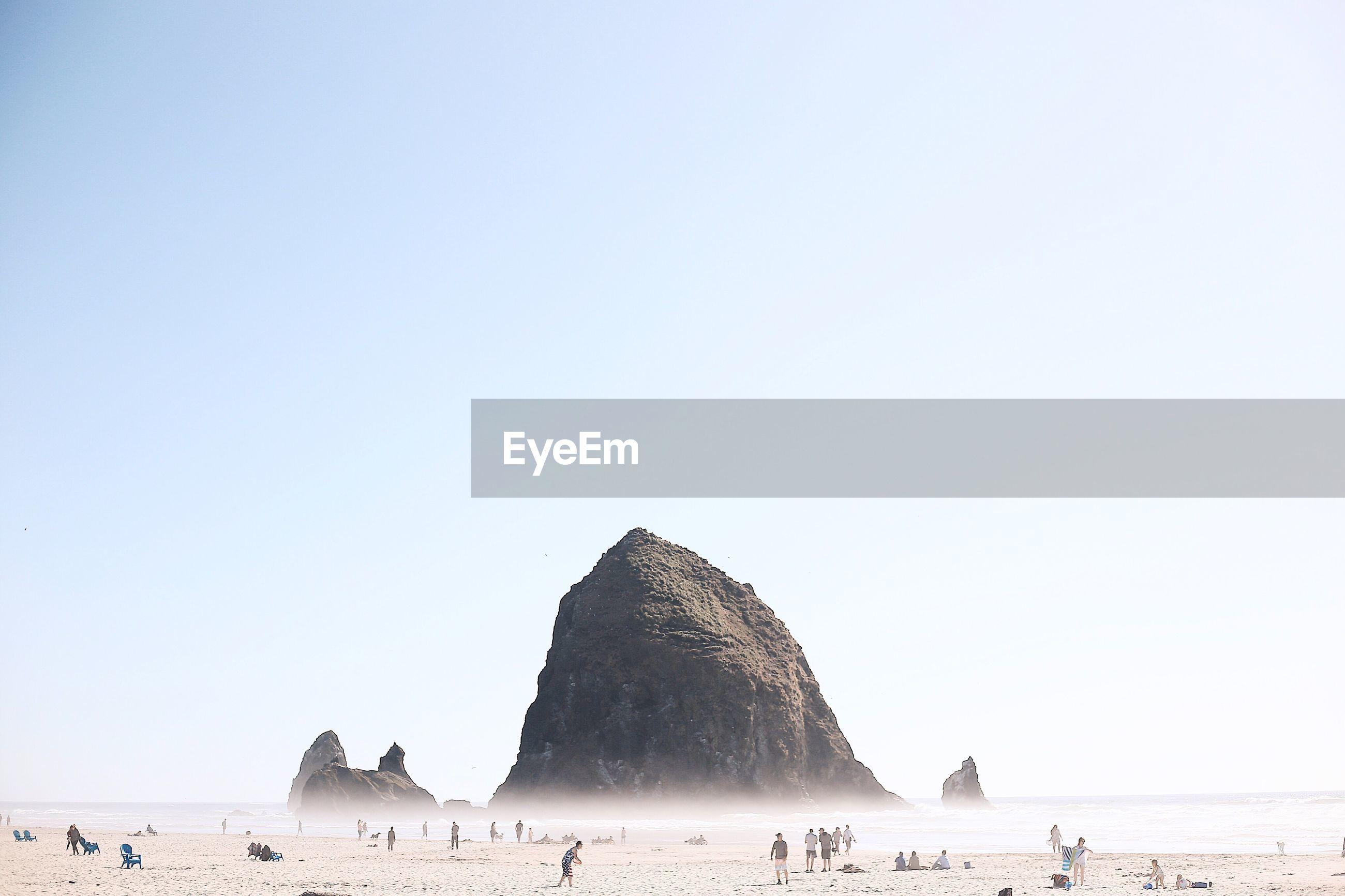 People on beach against clear sky