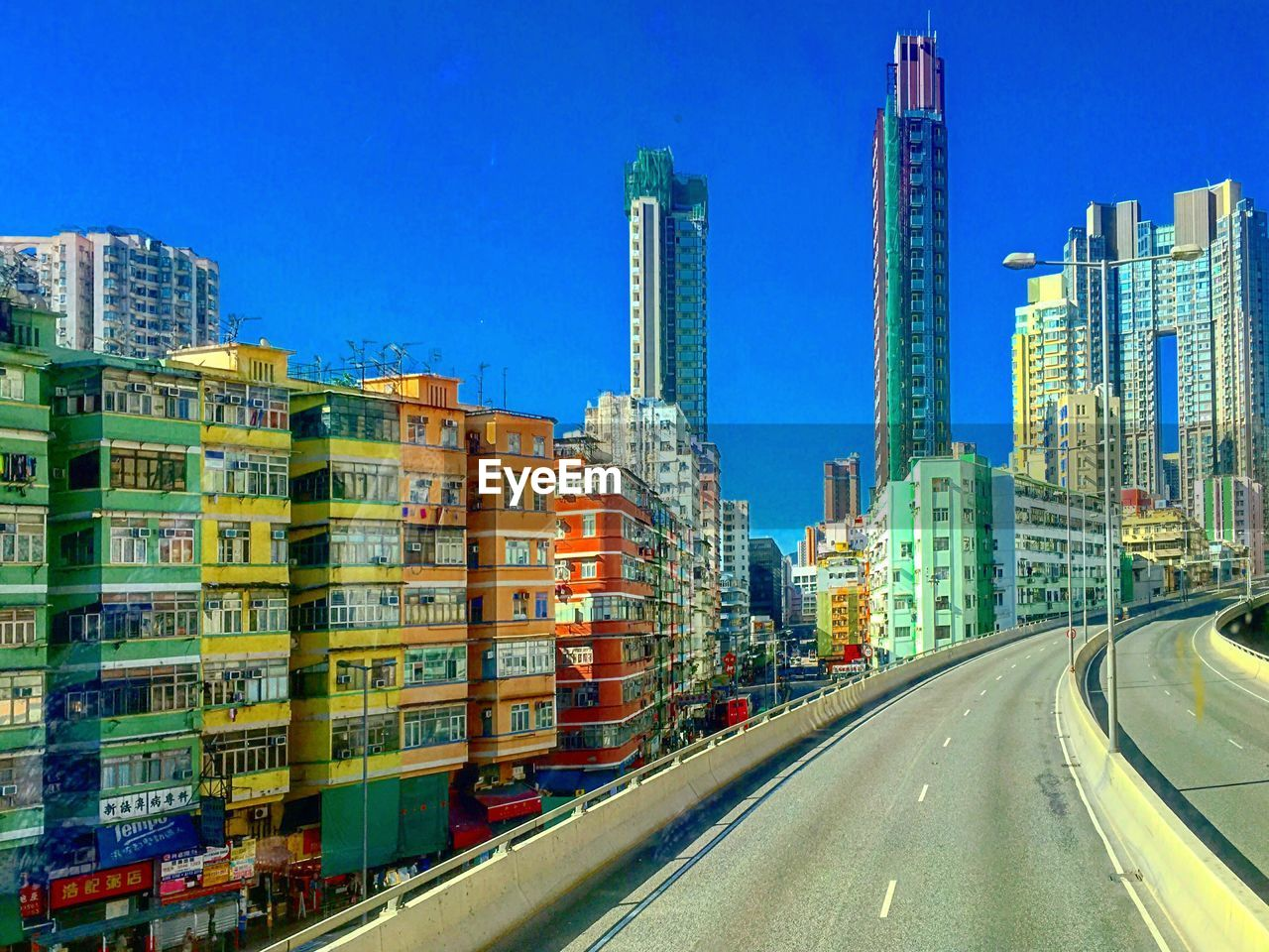Overpass by colorful buildings against clear sky