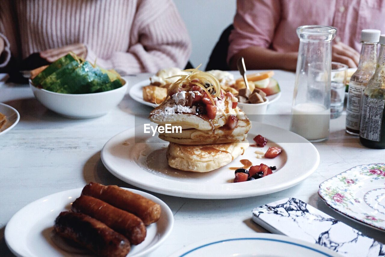 Food Served On Table With Men Sitting In Background