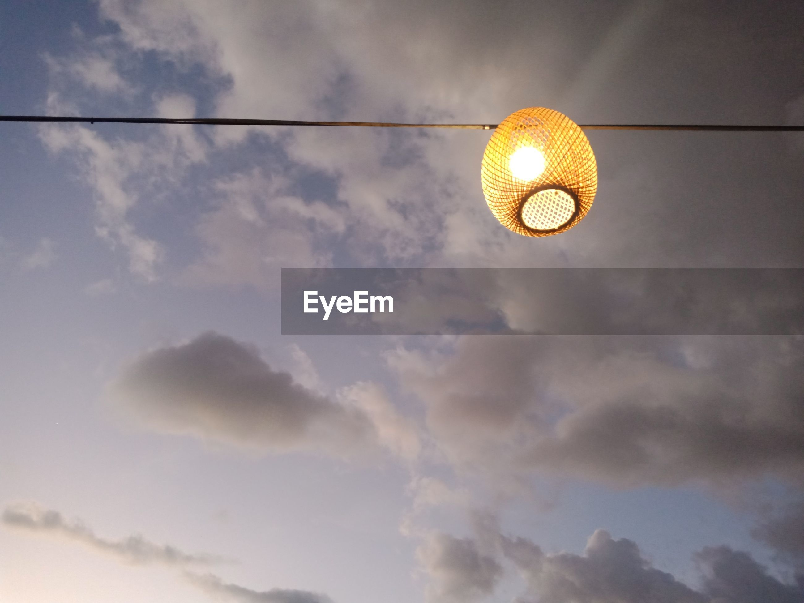 LOW ANGLE VIEW OF ILLUMINATED LAMP HANGING AGAINST SKY