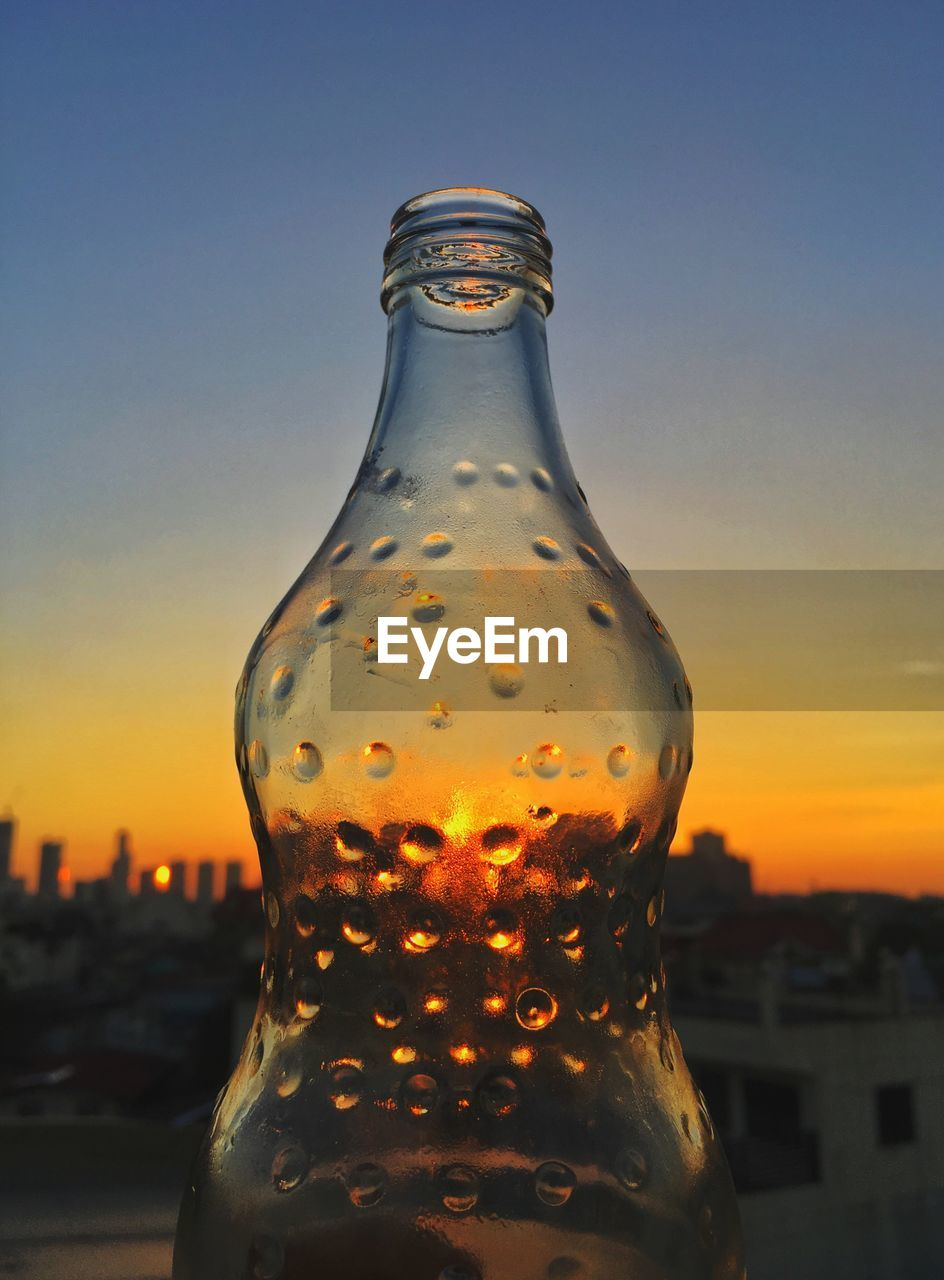 CLOSE-UP OF GLASS BOTTLE AGAINST SKY AT SUNSET