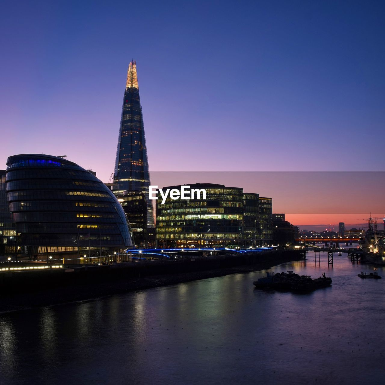 architecture, built structure, building exterior, illuminated, tower, travel destinations, skyscraper, night, city, cityscape, tourism, sunset, modern, travel, water, sky, river, urban skyline, waterfront, outdoors, no people, clear sky, nature