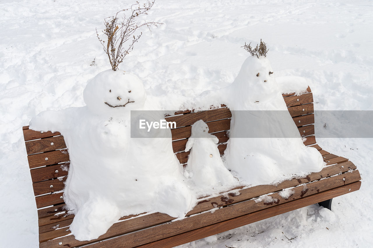 High Angle View Of Snowmen On Bench
