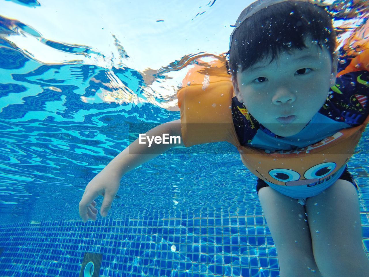 pool, childhood, child, swimming pool, water, leisure activity, one person, real people, lifestyles, boys, swimming, portrait, nature, day, front view, men, enjoyment, outdoors, innocence, eyewear