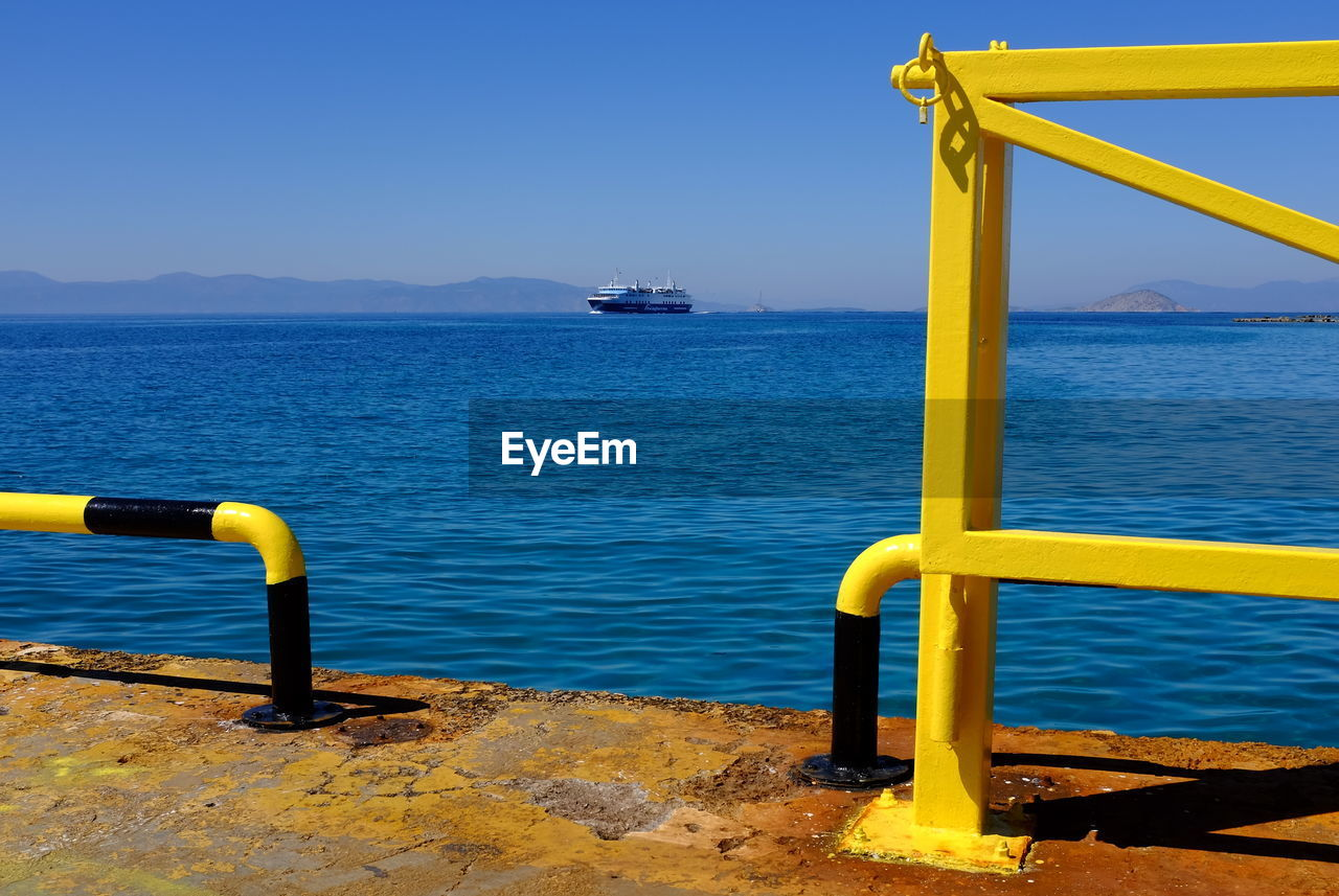 water, sky, yellow, sea, nature, metal, no people, beauty in nature, tranquil scene, day, scenics - nature, blue, outdoors, tranquility, clear sky, pier, railing, nautical vessel, transportation