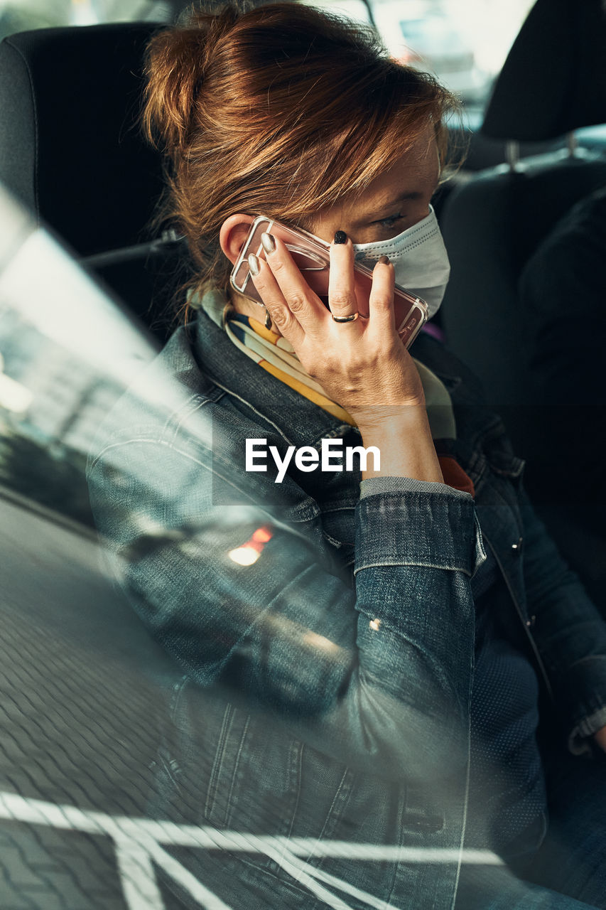 Woman wearing mask talking on phone sitting in car
