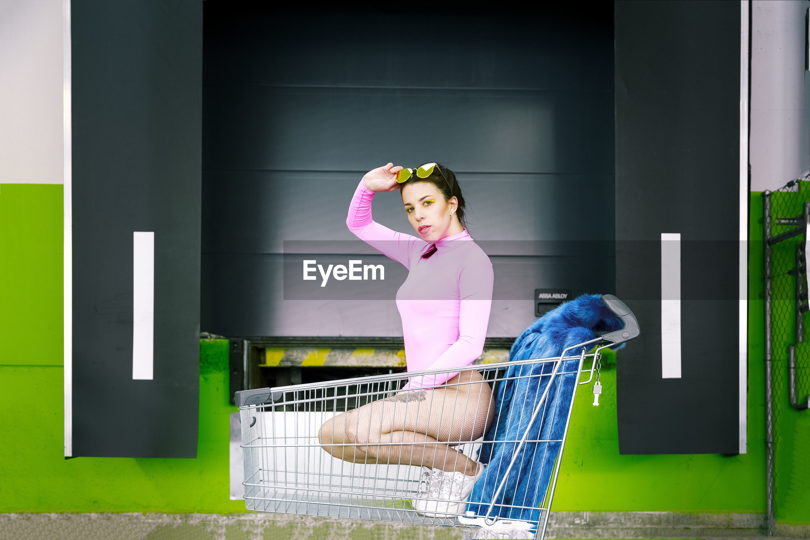 Portrait of sensuous woman crouching in shopping cart