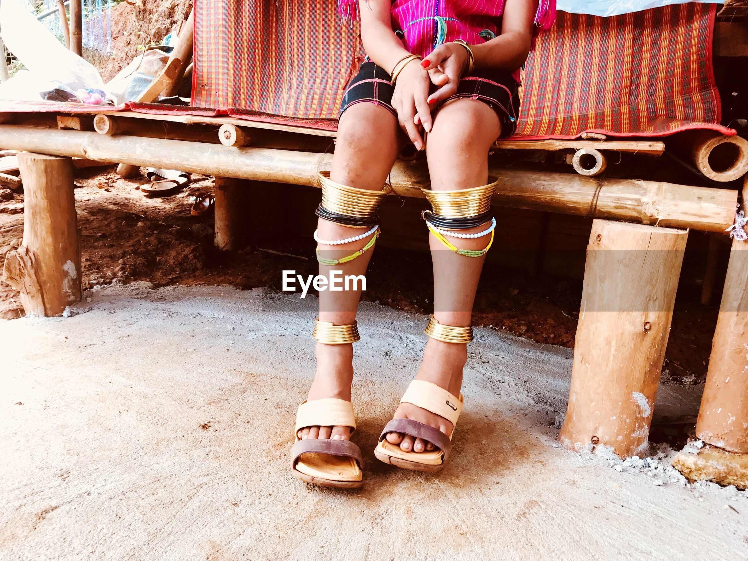 Low section of woman wearing anklets while sitting on bench