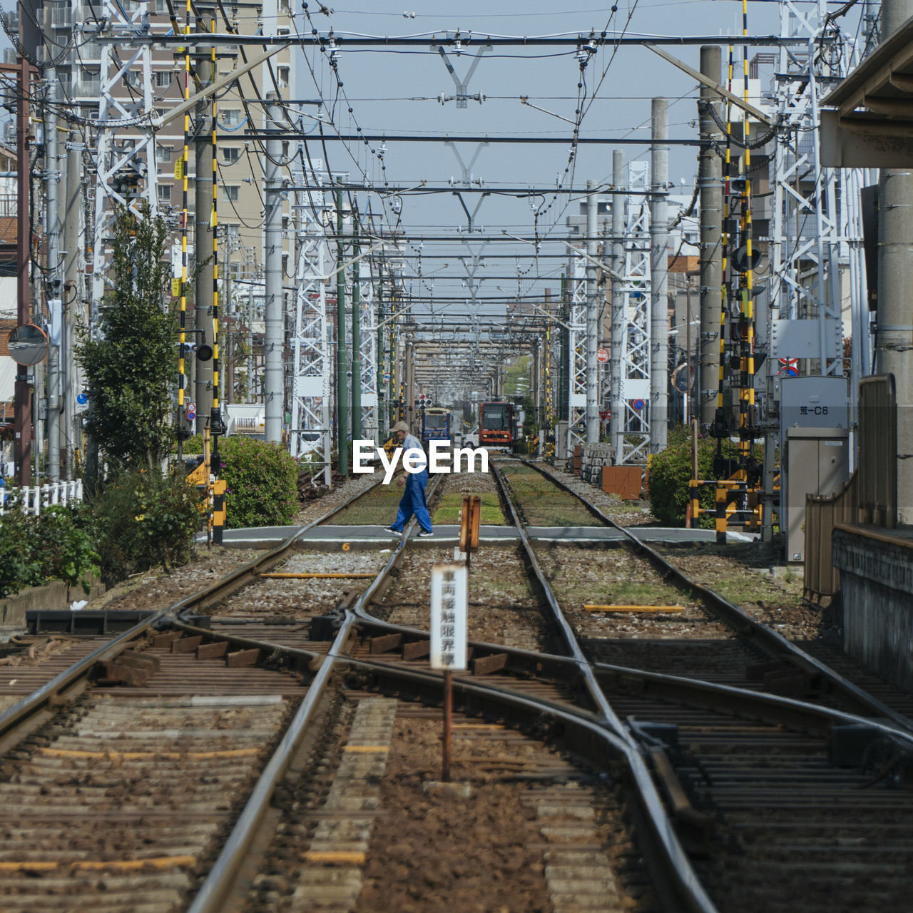 track, railroad track, rail transportation, architecture, built structure, building exterior, transportation, day, connection, real people, the way forward, direction, nature, mode of transportation, full length, one person, cable, technology, city, electricity, outdoors, power supply