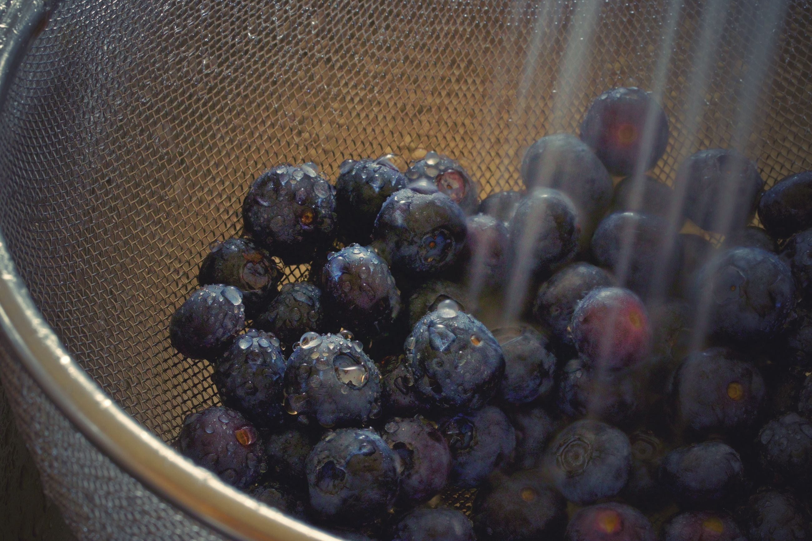 Close-up of running water over blueberries in colander