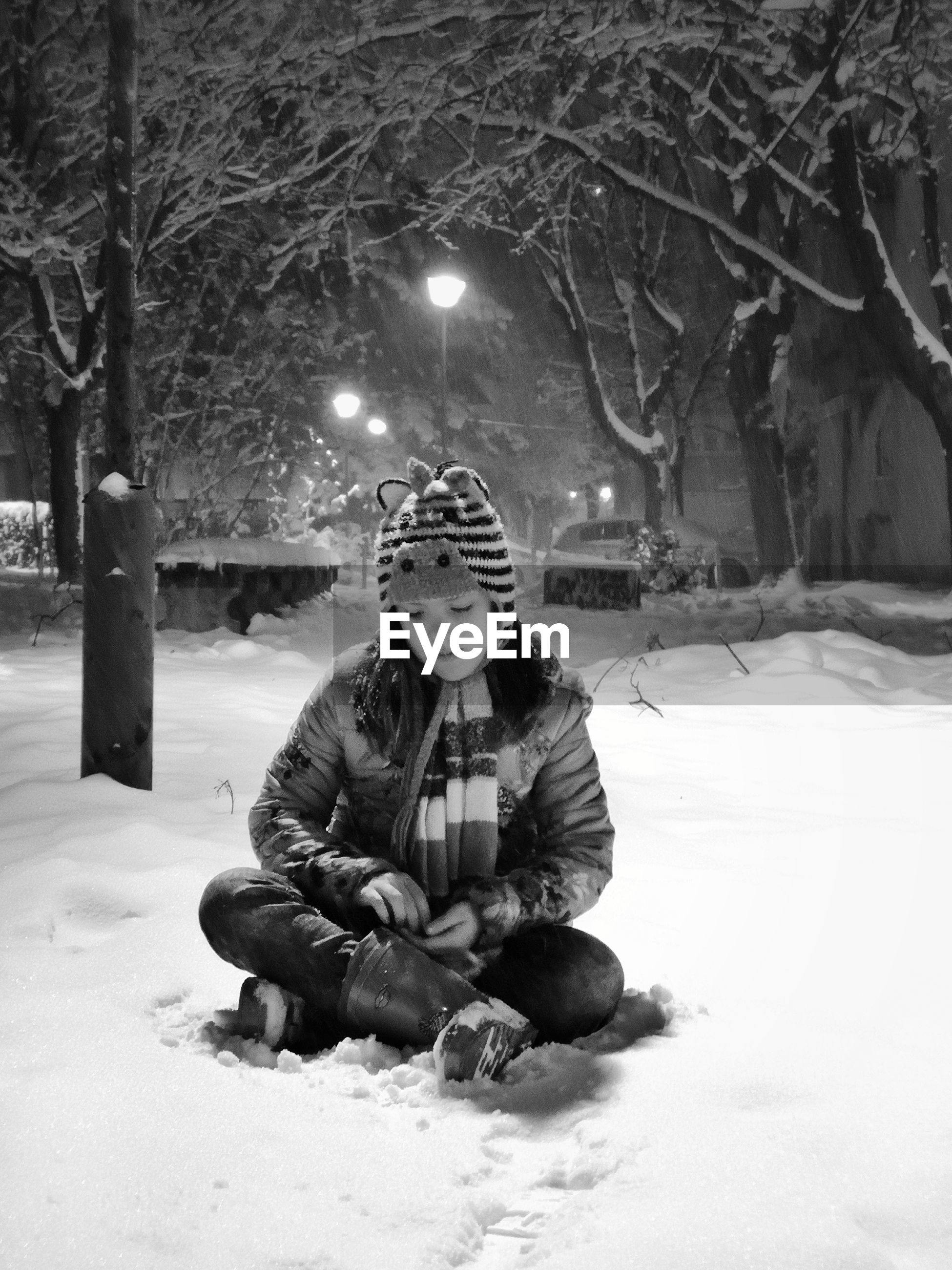 Cute girl sitting on snow at night