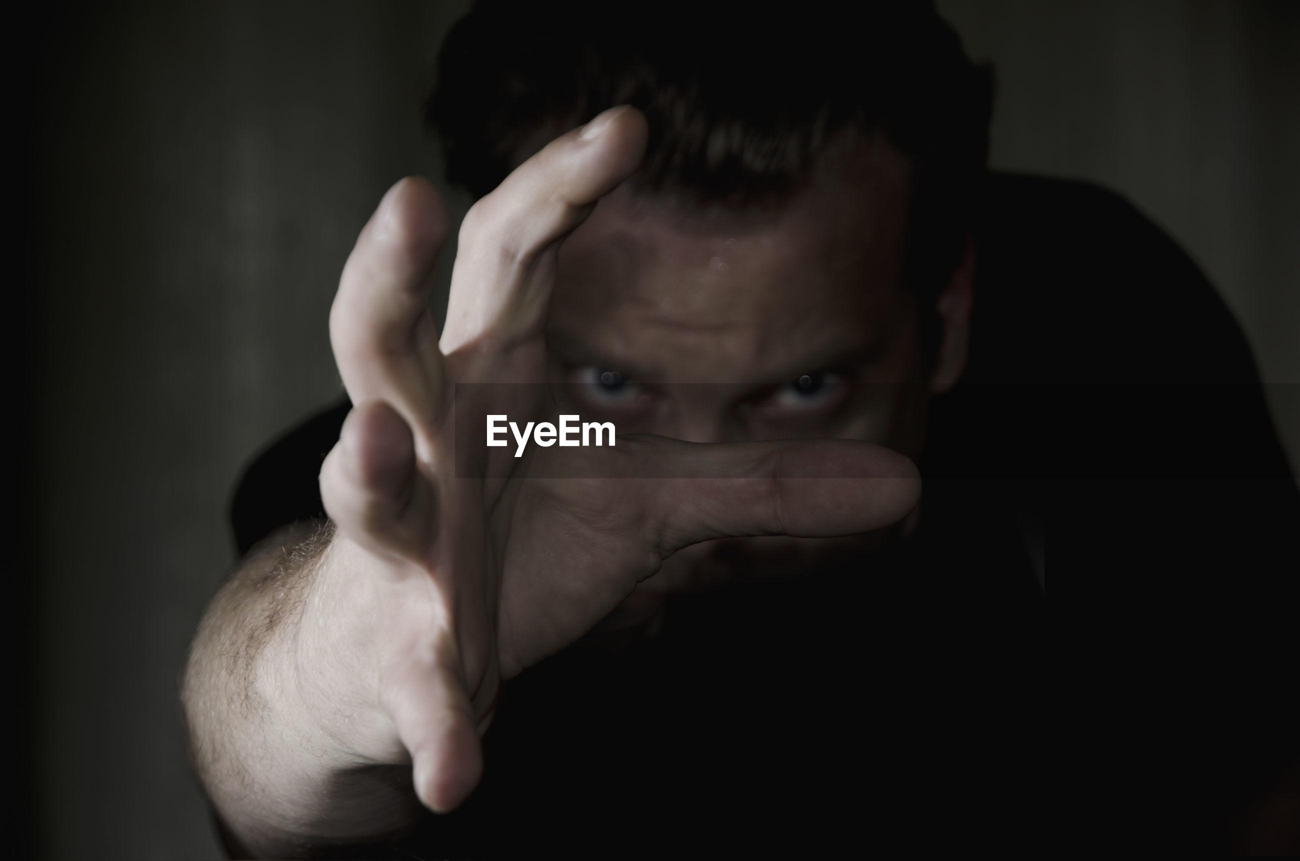 Close-up portrait of man gesturing in darkroom