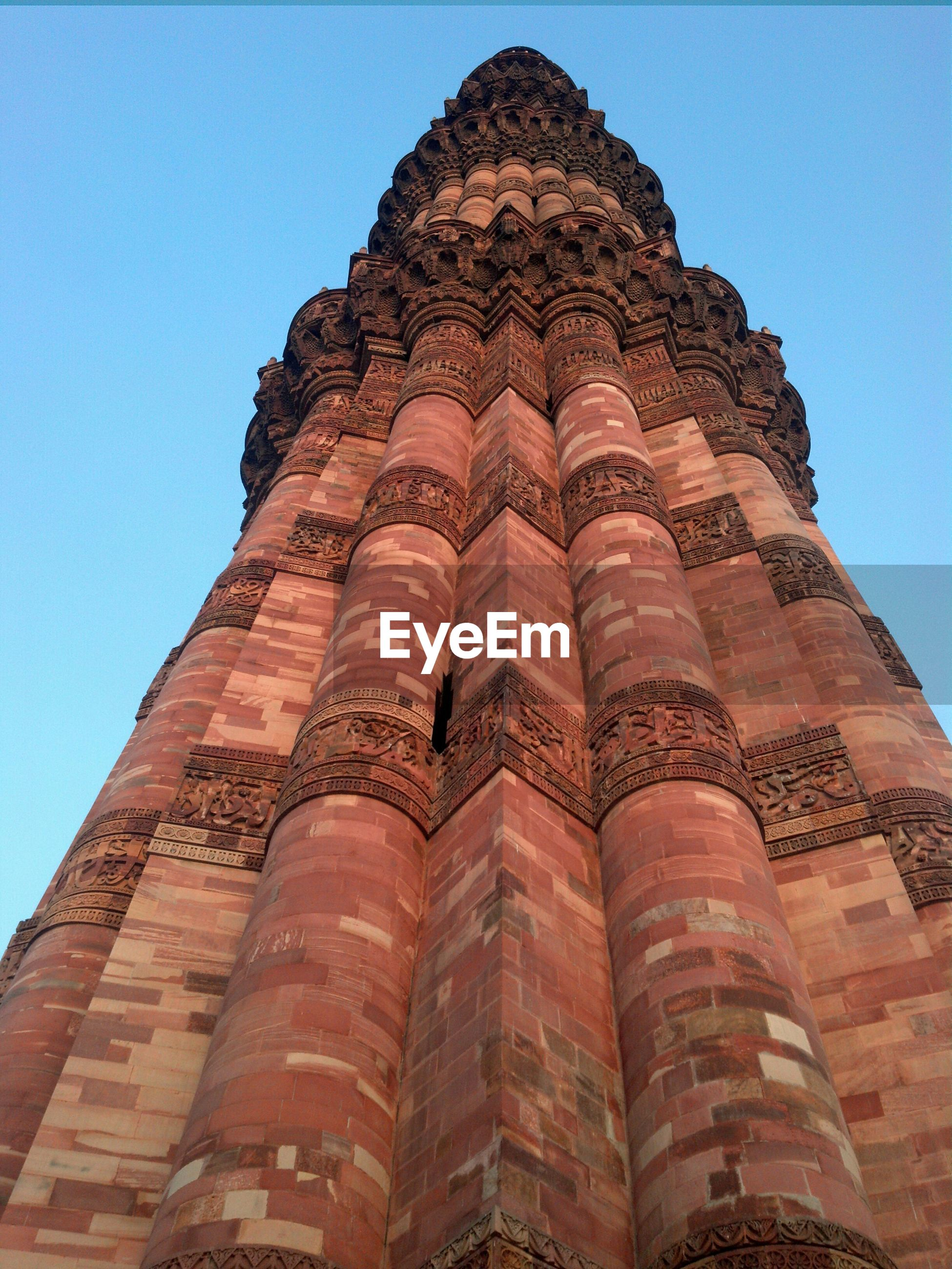 Low angle view of qutb minar against clear blue sky
