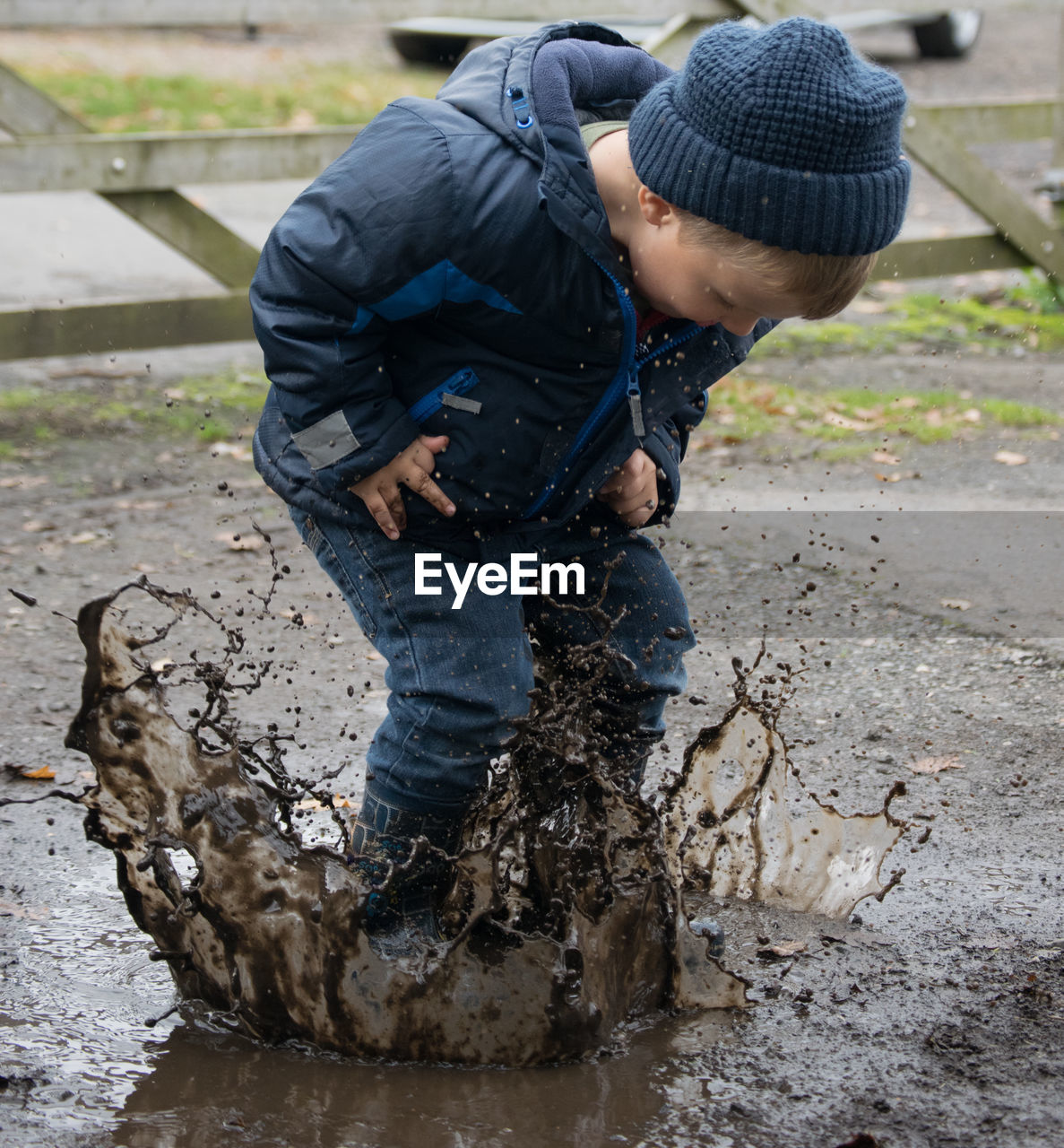 Full Length Of Boy Playing In Puddle