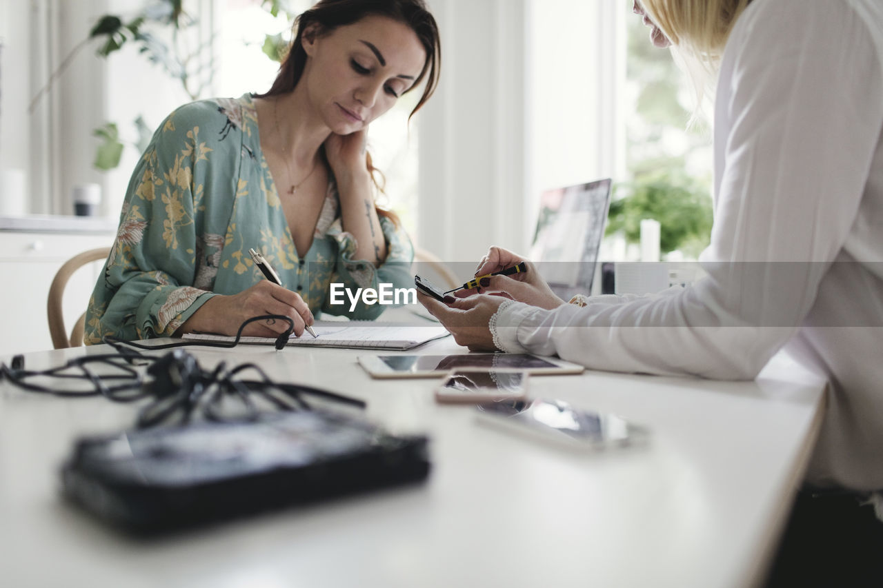 two people, adult, table, selective focus, real people, indoors, women, holding, technology, wireless technology, young women, connection, young adult, occupation, people, day, togetherness, working, business