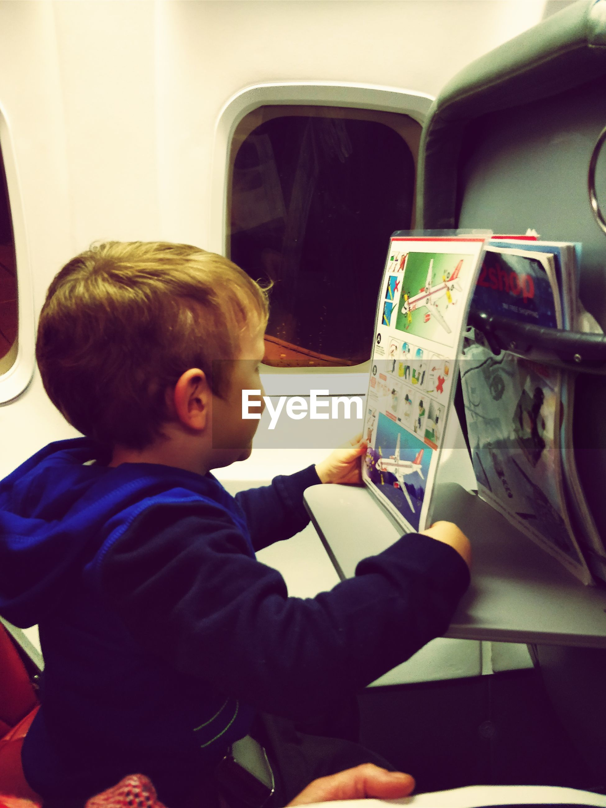 Side view of boy reading book in airplane