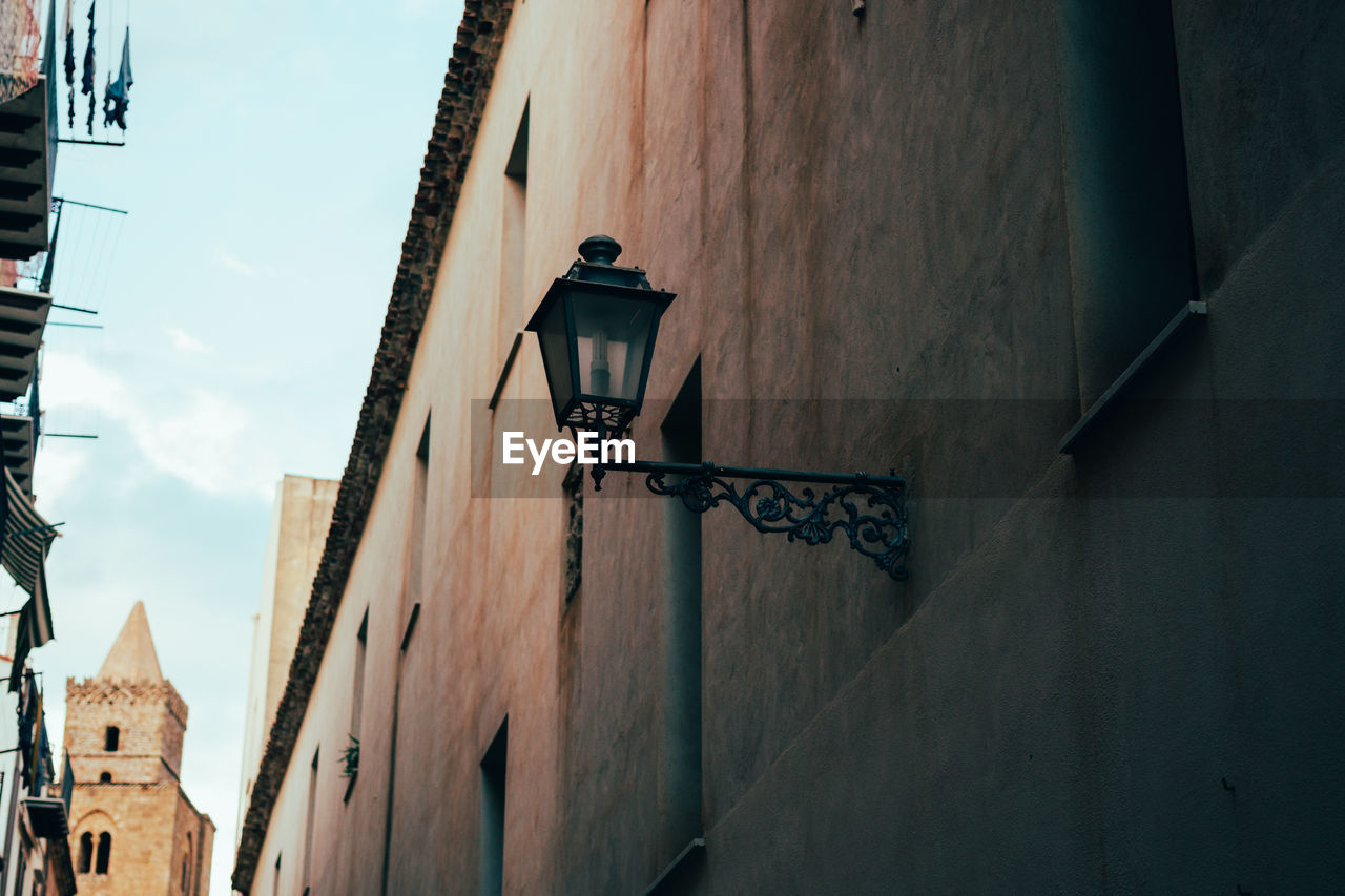 architecture, building exterior, built structure, low angle view, wall lamp, street light, outdoors, no people, gas light, day, sky