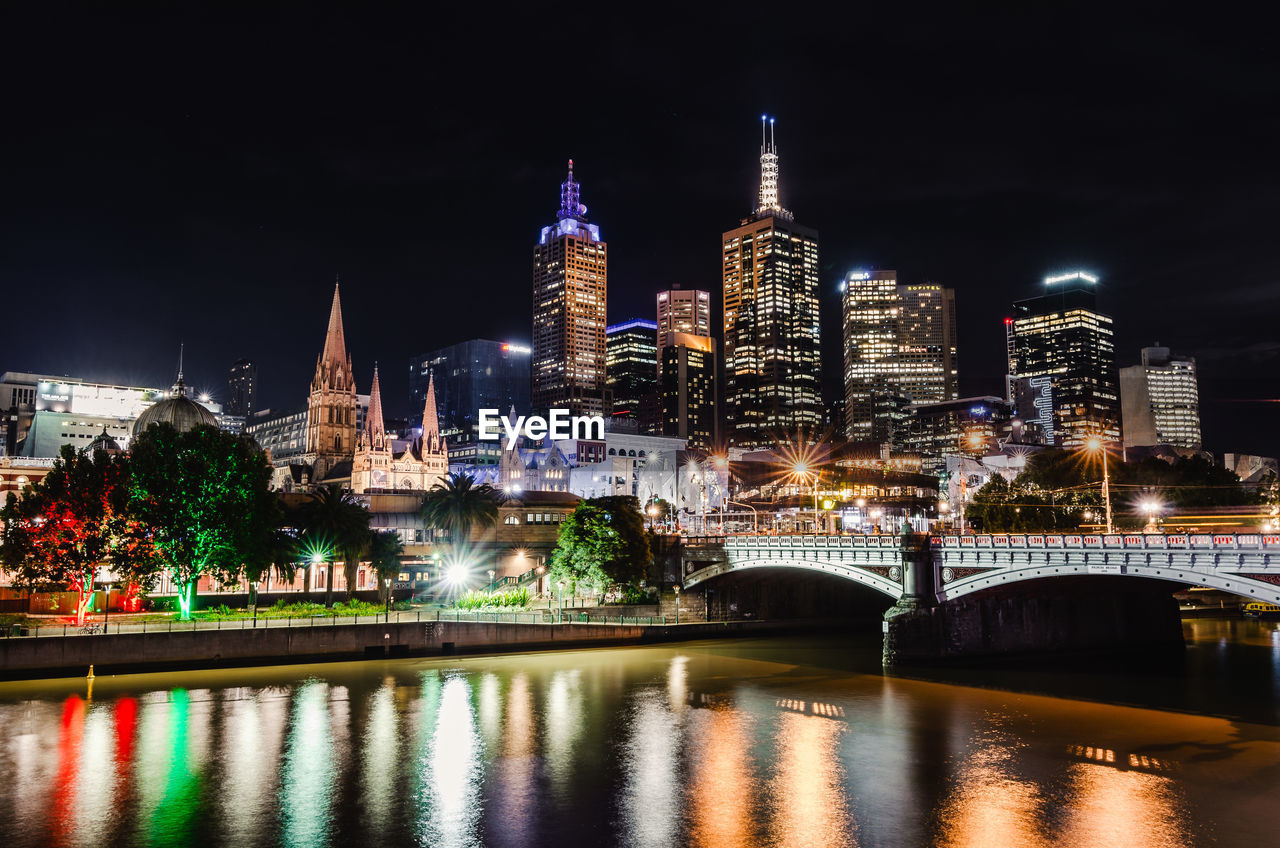 architecture, built structure, building exterior, night, illuminated, water, building, city, sky, river, waterfront, travel destinations, tower, tall - high, office building exterior, reflection, nature, skyscraper, no people, cityscape, outdoors, bridge - man made structure, modern, spire