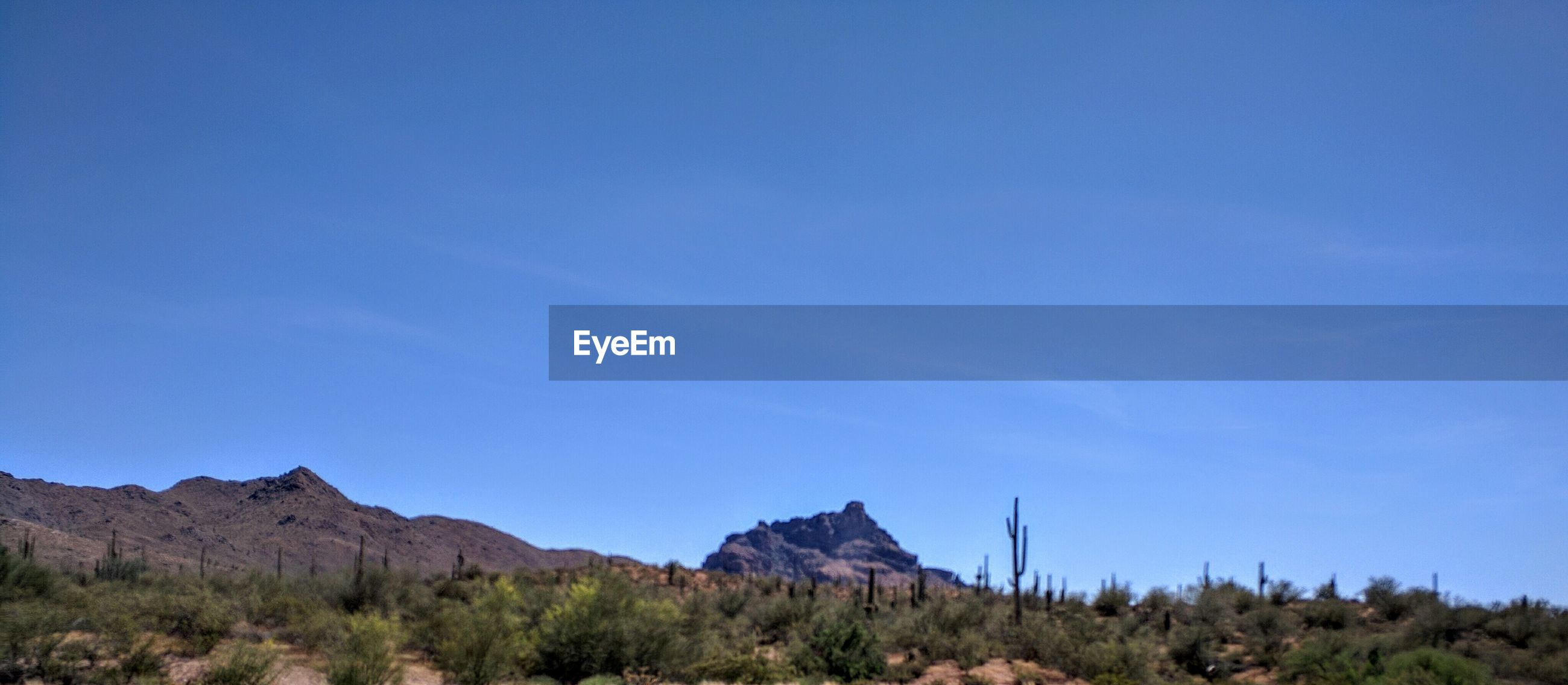 Scenic view of mountains against blue sky on sunny day