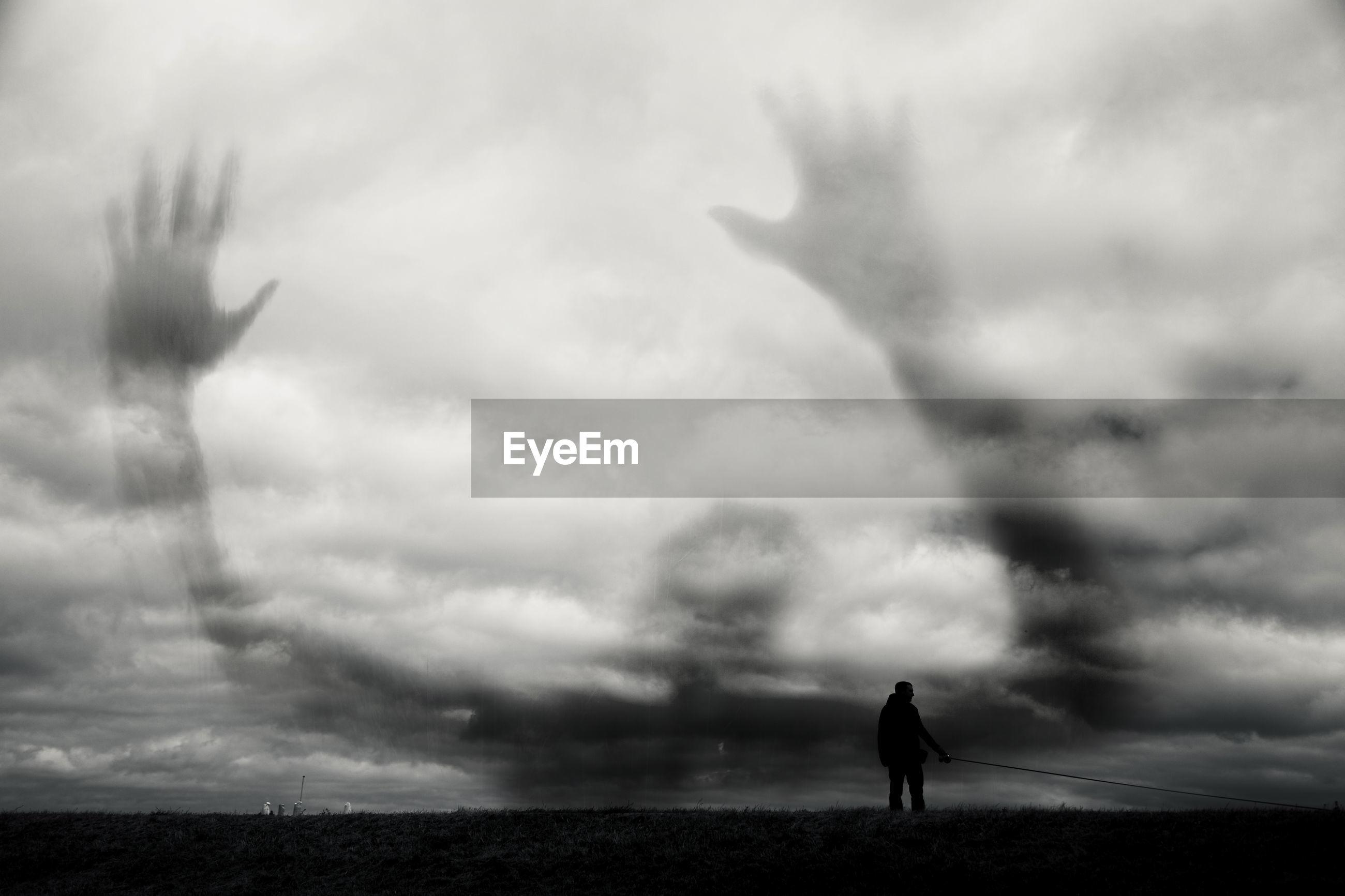 SILHOUETTE MAN WALKING AGAINST CLOUDY SKY