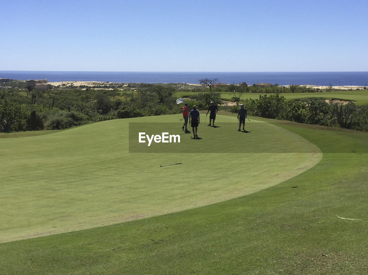 People standing on golf course against sky