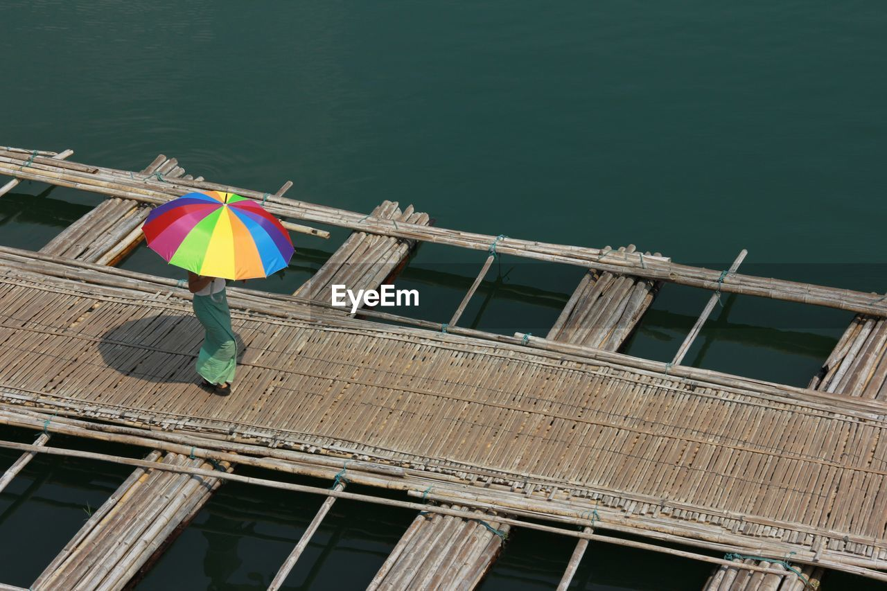 High angle view of woman with colorful umbrella walking on wooden bridge over lake