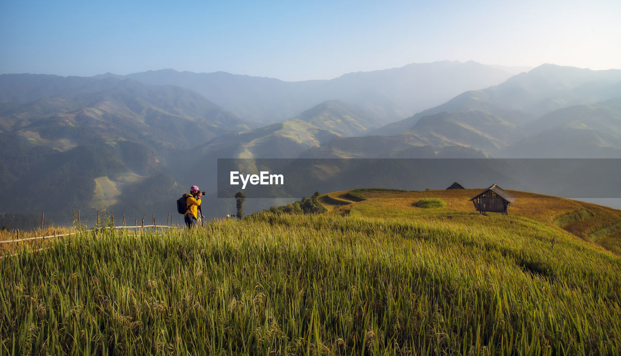 mountain, field, real people, agriculture, nature, men, one person, farmer, growth, beauty in nature, grass, landscape, lifestyles, outdoors, plant, tranquil scene, scenics, rice paddy, rice - cereal plant, tranquility, standing, sunset, adventure, sky, scarecrow, mountain range, occupation, day, clear sky, people