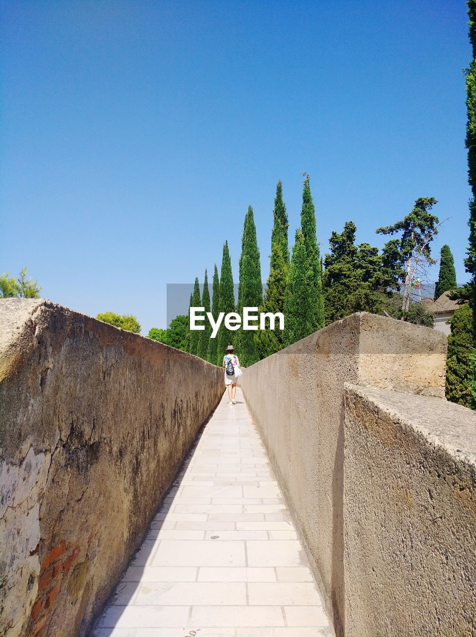 sky, clear sky, architecture, direction, the way forward, copy space, nature, day, built structure, blue, footpath, plant, real people, lifestyles, tree, diminishing perspective, sunlight, wall, outdoors, history