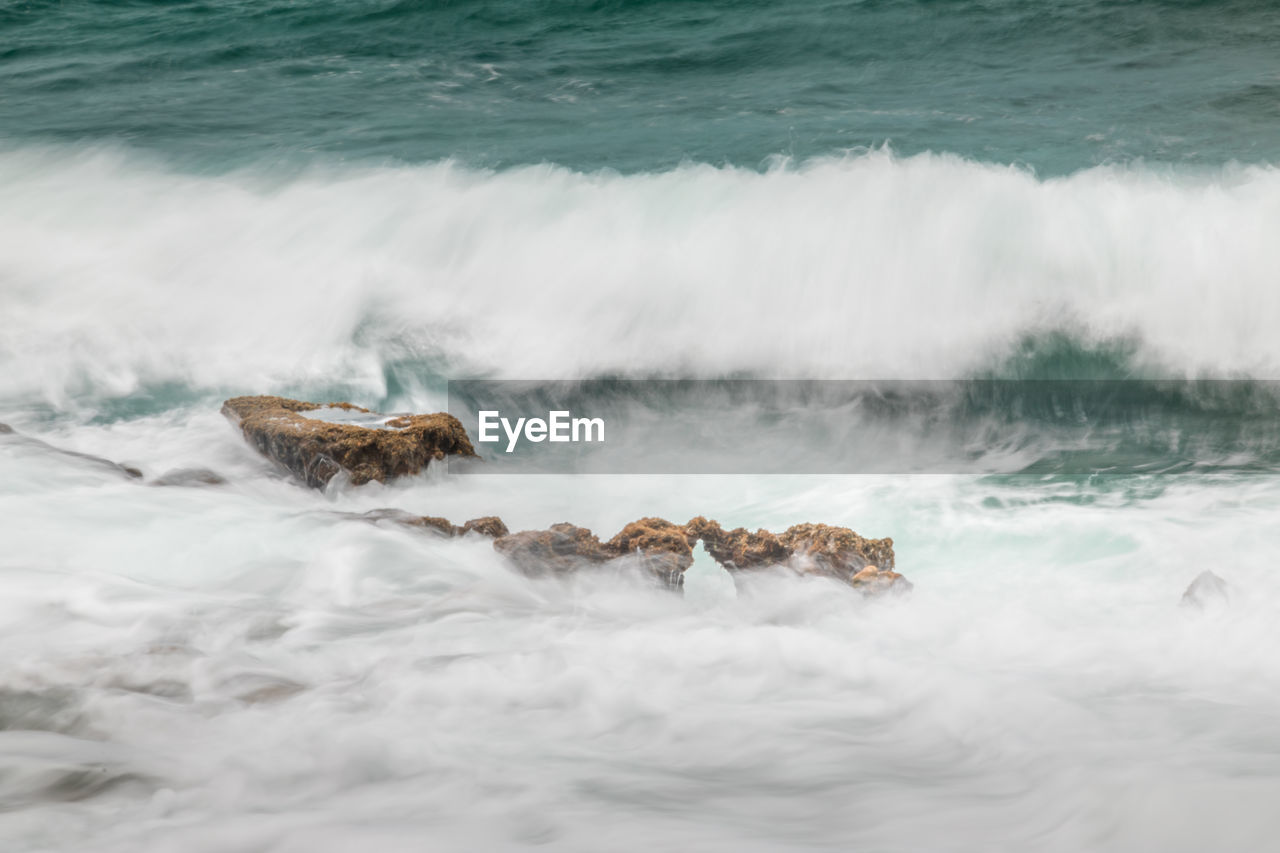 Rocks and cotton water on the coast of the cayman islands, long exposure