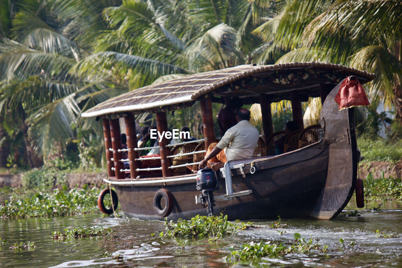 tropical climate, palm tree, water, real people, men, plant, tree, nature, transportation, nautical vessel, day, full length, people, mode of transportation, lifestyles, occupation, adult, outdoors