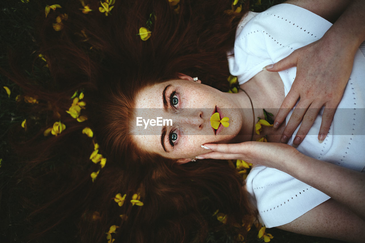 high angle view, lying down, lying on back, childhood, real people, looking at camera, portrait, relaxation, outdoors, day, young women, flower, young adult, close-up, nature, freshness, people