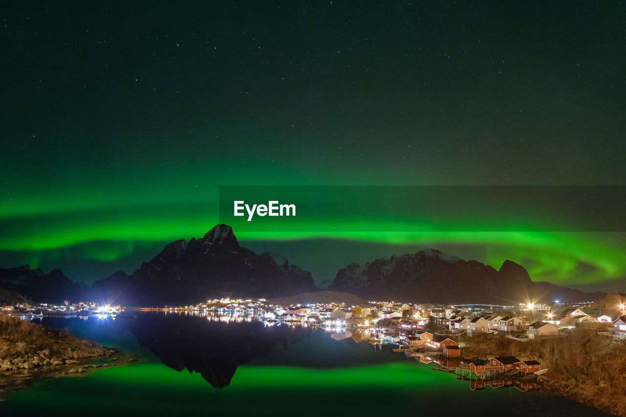 Aurora polaris over mountains against sky at night