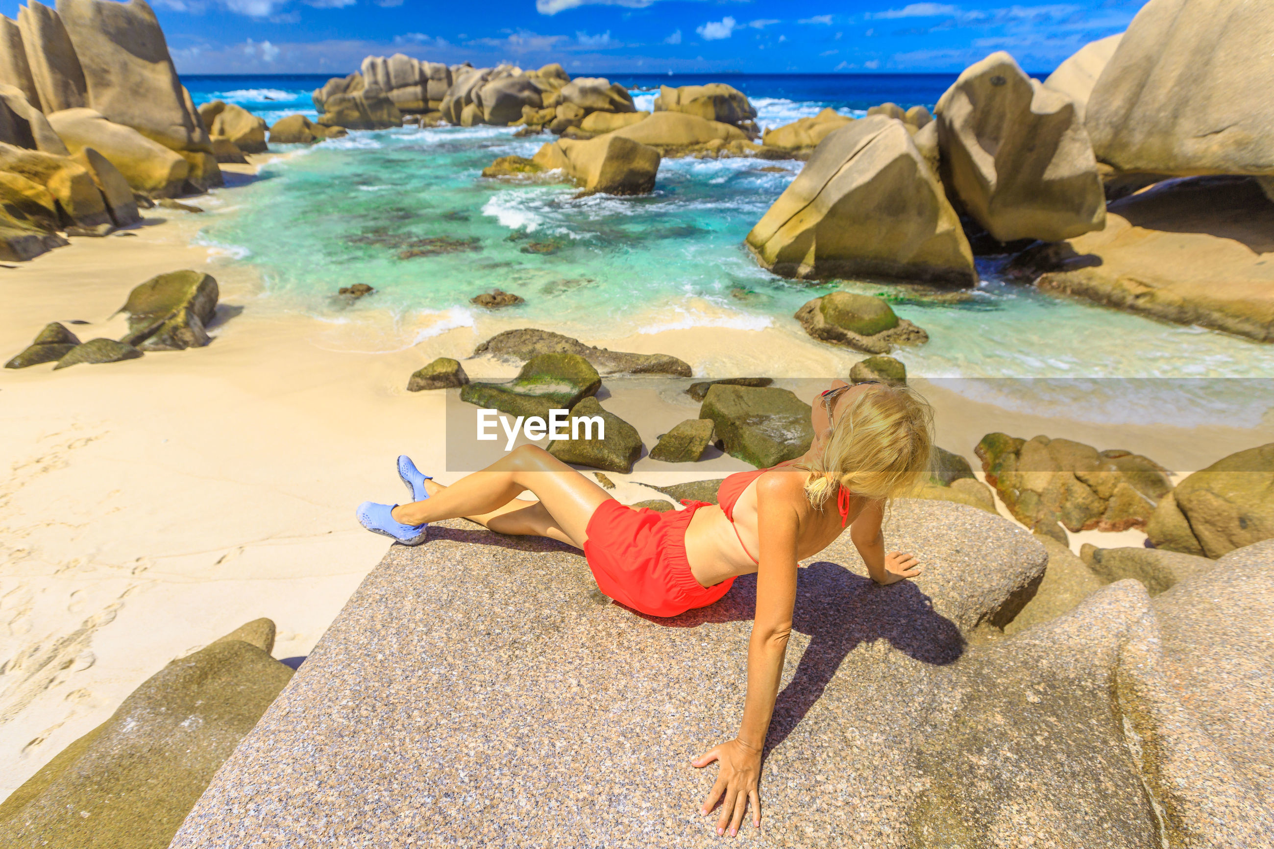 Full length of woman resting on rock at beach during summer