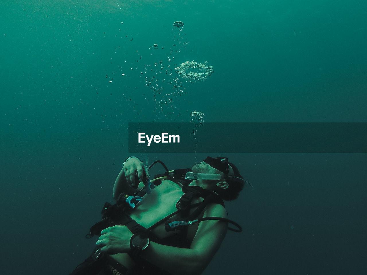 Shirtless Man Swimming Undersea