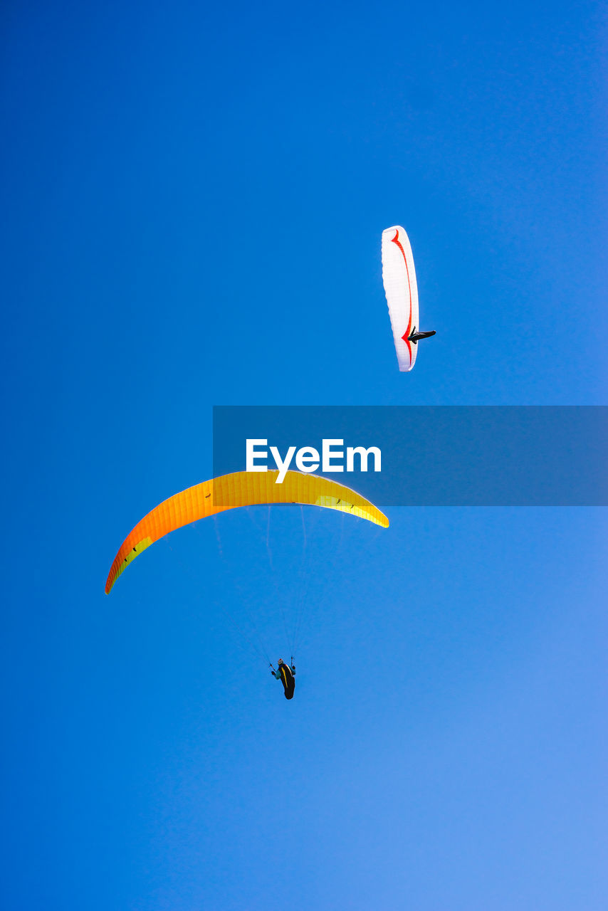 extreme sports, flying, sky, parachute, paragliding, sport, adventure, mid-air, blue, unrecognizable person, clear sky, leisure activity, real people, gliding, copy space, low angle view, transportation, freedom, nature, day, outdoors, skydiving