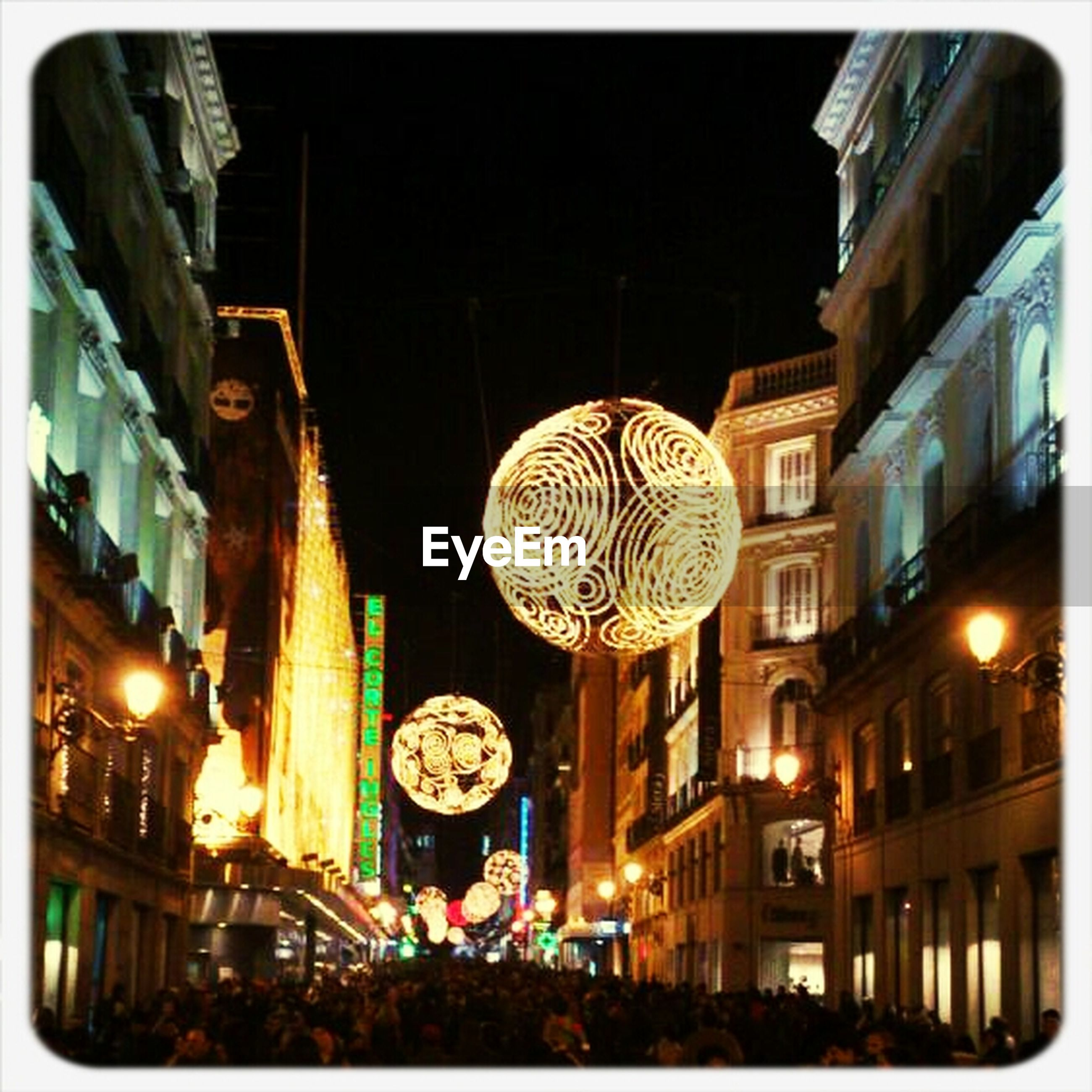 illuminated, night, transfer print, architecture, building exterior, built structure, low angle view, lighting equipment, city, auto post production filter, celebration, city life, street light, decoration, large group of people, sky, christmas, building, arts culture and entertainment, hanging