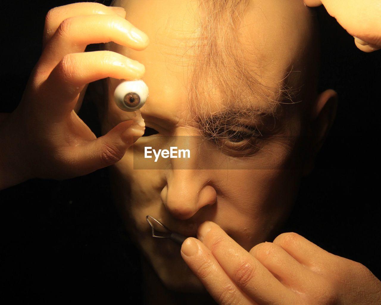 human eye, human body part, human hand, human face, close-up, real people, childhood, holding, make-up, black background, leisure activity, human nose, indoors, eyelash, eyebrow, eyesight, eyeball, young adult, young women, day, people