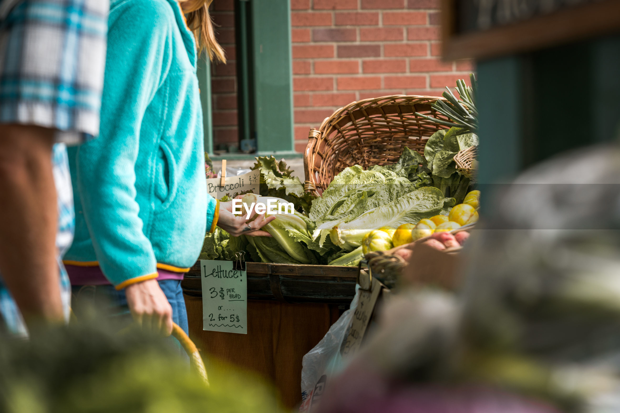MIDSECTION OF WOMAN STANDING BY MARKET