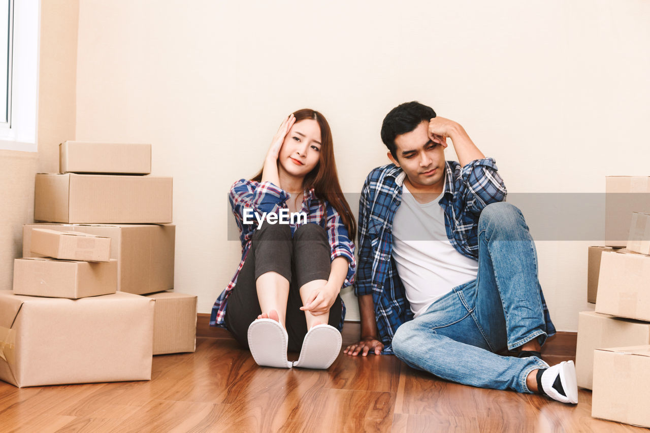 Worried Couple Sitting On Floor At New Home