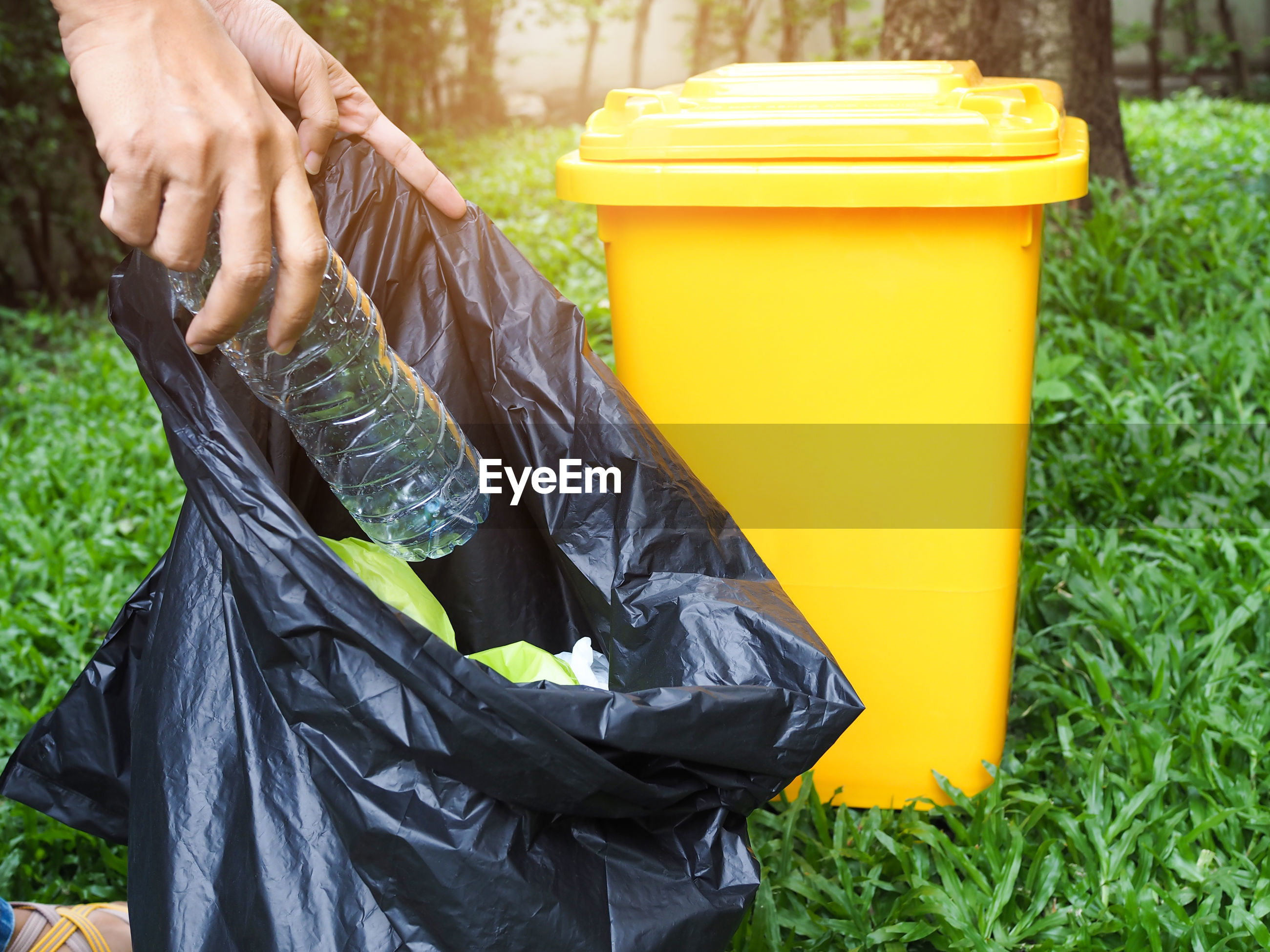 Cropped hands of person holding bottle in garbage bag by bin on grass