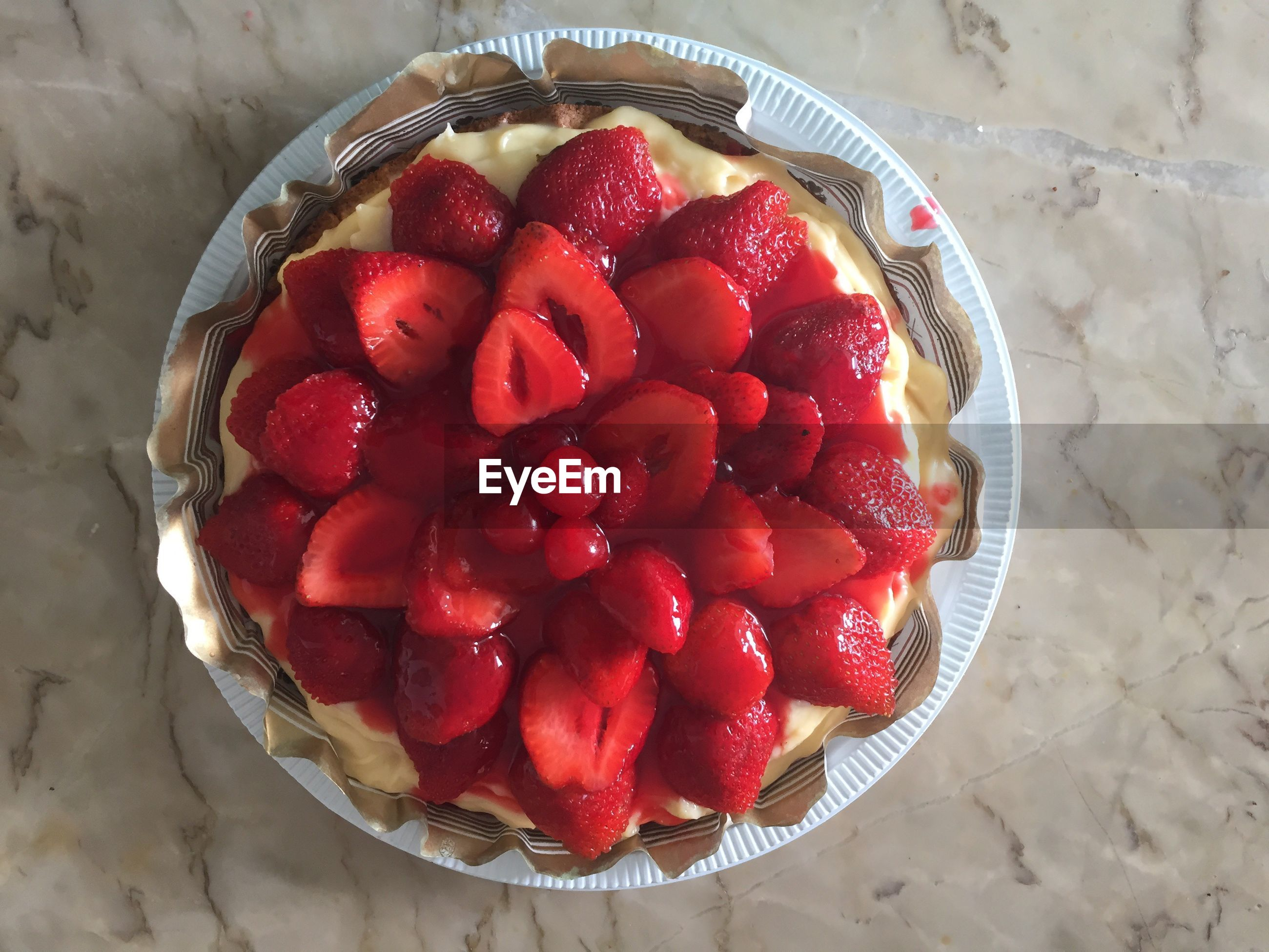 Directly above shot of strawberry tart in plate on marble